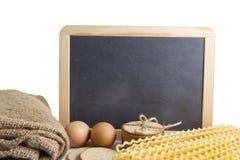 Οργανικά κίτρινα μακροχρόνια σπείρες και αυγό ζυμαρικών με το μαύρο υπόβαθρο πινάκων για το κείμενο Στοκ εικόνες με δικαίωμα ελεύθερης χρήσης