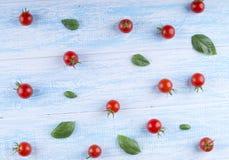 Οργανικές κόκκινες ντομάτες κερασιών στο μπλε υπόβαθρο Κόκκινες ντομάτες και Στοκ Εικόνα