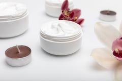 Οργανική κρέμα στα εμπορευματοκιβώτια με τις ορχιδέες και τα κεριά που απομονώνονται στο λευκό στοκ φωτογραφία με δικαίωμα ελεύθερης χρήσης