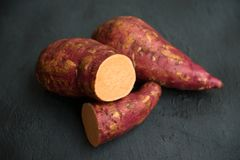 Οργανική πορτοκαλιά γλυκιά πατάτα στο σκοτεινό υπόβαθρο στοκ φωτογραφίες