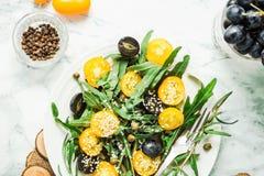 Οργανική πράσινη σαλάτα με το arugula, κίτρινες ντομάτες, ελιές, sesam Στοκ Φωτογραφίες