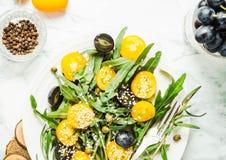 Οργανική πράσινη σαλάτα με το arugula, κίτρινες ντομάτες, ελιές, sesam Στοκ Εικόνα