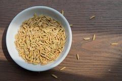 Οργανικοί σπόροι ορυζώνα, ρύζι και άσπρο ρύζι στο ξύλινο υπόβαθρο στοκ εικόνα