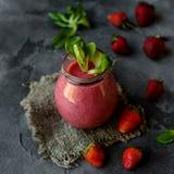 Οργανικός καταφερτζής φρούτων φραουλών με τα πράσινα φύλλα στοκ φωτογραφίες