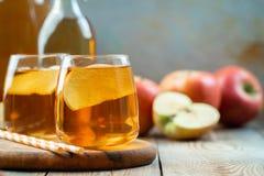 Οργανικός μηλίτης ή χυμός της Apple σε έναν ξύλινο πίνακα με το διάστημα αντιγράφων Δύο γυαλιά με τα φύλλα ποτών και φθινοπώρου σ στοκ εικόνες