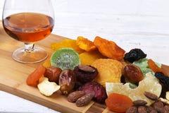 Οργανικός υγιής ανάμεικτος ξηρός - τα φρούτα και τα γυαλιά με το κονιάκ ή το ουίσκυ στο κρασί επιβιβάζονται r στοκ εικόνα