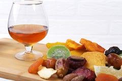 Οργανικός υγιής ανάμεικτος ξηρός - τα φρούτα και τα γυαλιά με το κονιάκ ή το ουίσκυ στο κρασί επιβιβάζονται r στοκ εικόνες με δικαίωμα ελεύθερης χρήσης