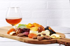 Οργανικός υγιής ανάμεικτος ξηρός - τα φρούτα και τα γυαλιά με το κονιάκ ή το ουίσκυ στο κρασί επιβιβάζονται r στοκ εικόνες