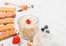 Οργανικός φραγμός granola δημητριακών με τα μούρα με το κουτάλι μελιού και το βάζο των βρωμών στο μαρμάρινο υπόβαθρο Τοπ όψη Φράο στοκ φωτογραφία