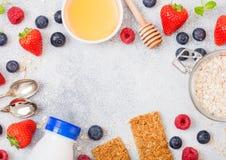 Οργανικός φραγμός granola δημητριακών με τα μούρα με το κουτάλι μελιού και το βάζο των βρωμών και το μπουκάλι του ποτού γάλακτος  στοκ εικόνα με δικαίωμα ελεύθερης χρήσης