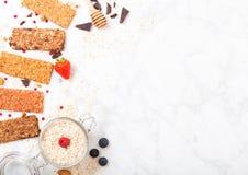 Οργανικός φραγμός granola δημητριακών με τα μούρα με το κουτάλι μελιού και το βάζο των βρωμών στο μαρμάρινο υπόβαθρο Τοπ όψη Φράο στοκ εικόνα με δικαίωμα ελεύθερης χρήσης