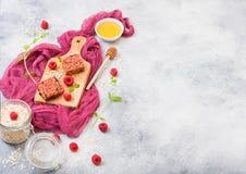 Οργανικός φραγμός granola φρούτων δημητριακών με τα μούρα στον εκλεκτής ποιότητας πίνακα με το κουτάλι μελιού και το βάζο των βρω στοκ εικόνες