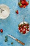 Οργανικό γιαούρτι σε ένα κύπελλο με τις πρόσφατα κομμένες φράουλες σε ένα μπλε Στοκ φωτογραφίες με δικαίωμα ελεύθερης χρήσης
