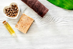 Οργανικό σαπούνι καφέ, σιτάρια καφέ, έλαιο και πετσέτα στην ξύλινη τοπ άποψη υποβάθρου copyspace Στοκ φωτογραφία με δικαίωμα ελεύθερης χρήσης