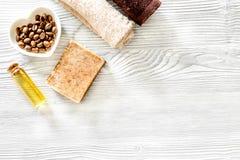 Οργανικό σαπούνι καφέ, σιτάρια καφέ, έλαιο και πετσέτα στην ξύλινη τοπ άποψη υποβάθρου copyspace Στοκ Εικόνα