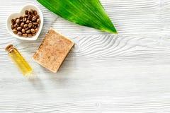 Οργανικό σαπούνι καφέ, σιτάρια καφέ και πετσέτα στην ξύλινη τοπ άποψη υποβάθρου copyspace Στοκ εικόνα με δικαίωμα ελεύθερης χρήσης