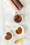 Οργανικό σαπούνι καφέ, σιτάρια καφέ και πετσέτα στην ξύλινη τοπ άποψη υποβάθρου Στοκ Φωτογραφία