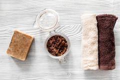 Οργανικό σαπούνι καφέ, σιτάρια καφέ και πετσέτα στην ξύλινη τοπ άποψη υποβάθρου Στοκ Φωτογραφίες