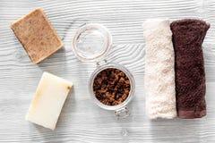 Οργανικό σαπούνι καφέ, σιτάρια καφέ και πετσέτα στην ξύλινη τοπ άποψη υποβάθρου Στοκ Εικόνες