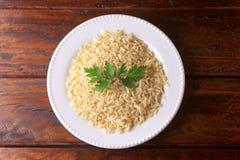Οργανικό σιτάρι καφετιού ρυζιού που μαγειρεύεται στο άσπρο πιάτο στον αγροτικό ξύλινο πίνακα Ακέραιο ρύζι στοκ φωτογραφίες με δικαίωμα ελεύθερης χρήσης
