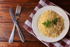 Οργανικό σιτάρι καφετιού ρυζιού που μαγειρεύεται στο άσπρο πιάτο στον αγροτικό ξύλινο πίνακα Ακέραιο ρύζι στοκ φωτογραφία με δικαίωμα ελεύθερης χρήσης
