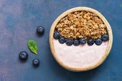 Οργανικό σπιτικό granola προγευμάτων από τις βρώμες με το γιαούρτι και τα βακκίνια σε ένα κεραμικό κύπελλο, μπλε υπόβαθρο Άποψη ά στοκ εικόνες
