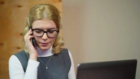 Οργανωμένος γραμματέας που απαντά στις κλήσεις και που εργάζεται στο lap-top υπάλληλος γραφείων φιλμ μικρού μήκους