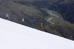 Ορειβάτες βουνών που κατεβαίνουν τη χιονώδη κλίση Στοκ φωτογραφία με δικαίωμα ελεύθερης χρήσης