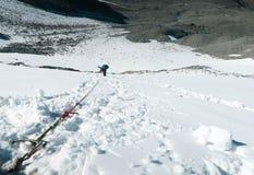 Ορειβάτης βουνών που πηγαίνει κάτω από τον κάθετο τοίχο Αναρρίχηση του εξοπλισμού Χιονώδες πέρασμα βουνών στοκ φωτογραφίες