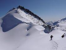 Ορειβάτης βουνών που φέρνει πολύ εξοπλισμό αναρρίχησης στη σειρά βουνών Mischabel στις ελβετικές Άλπεις επάνω από την αμοιβή Saas στοκ φωτογραφίες