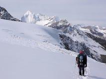 Ορειβάτης βουνών που φέρνει πολύ εξοπλισμό αναρρίχησης στη σειρά βουνών Mischabel στις ελβετικές Άλπεις επάνω από την αμοιβή Saas στοκ φωτογραφία με δικαίωμα ελεύθερης χρήσης