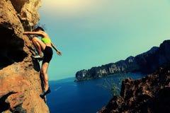 Ορειβάτης βράχου γυναικών που αναρριχείται στο βράχο βουνών παραλιών Στοκ Φωτογραφίες