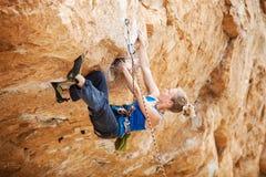 Ορειβάτης βράχου που αγωνίζεται να αποτελέσει την επόμενη μετακίνηση Στοκ Εικόνες