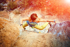 Ορειβάτης βράχου που αναρριχείται επάνω σε έναν απότομο βράχο στοκ φωτογραφία