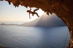 Ορειβάτης βράχου που αναρριχείται κατά μήκος της στέγης στη σπηλιά στο ηλιοβασίλεμα Στοκ Εικόνες