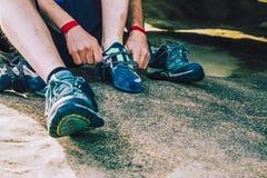 Ορειβάτης βράχου που βάζει αναρριμένος στα παπούτσια επάνω Στοκ φωτογραφία με δικαίωμα ελεύθερης χρήσης