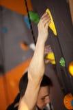 Ορειβάτης βράχου στον τεχνητό τοίχο αναρρίχησης Στοκ Φωτογραφίες