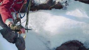 Ορειβάτης κάτω από τη ρωγμή βουνών, που κλίνει σε ετοιμότητα του και μια επιλογή πάγου Έχει ένα σακίδιο πλάτης στους ώμους και τη απόθεμα βίντεο