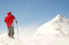 Ορειβάτης που αντιμετωπίζει τον αέρα και το χιόνι στην κορυφή βουνών στοκ φωτογραφίες