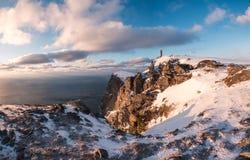 Ορειβάτης που στέκεται στην αιχμή του βουνού βράχου το χειμώνα στο ηλιοβασίλεμα στοκ φωτογραφία