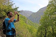 Ορειβάτης στα βουνά που παίρνουν τις φωτογραφίες στοκ φωτογραφία