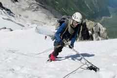Ορειβάτης στην κορυφή χιονιού, τις δύσκολους αιχμές βουνών και τον παγετώνα Στοκ Εικόνες