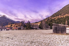 Ορεινό χωριό και παγωμένο λιβάδι στο σούρουπο Στοκ Φωτογραφία