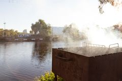 Ορειχαλκουργός σχαρών με το βαρύ καπνό κατά τη διάρκεια του ψησίματος στη σχάρα του κρέατος BBQ υπαίθριο κόμμα κοντά στη λίμνη ή  Στοκ Εικόνες