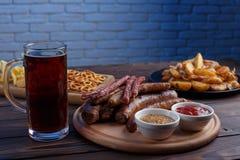 Ορεκτικά πρόχειρα φαγητά μπύρας καθορισμένα Ψημένα στη σχάρα λουκάνικα και ψημένες πατάτες Στοκ εικόνες με δικαίωμα ελεύθερης χρήσης
