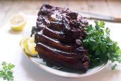 Ορεκτικά ψημένα βερνικωμένα πλευρά μοσχαρίσιων κρεάτων ή χοιρινού κρέατος που εξυπηρετούνται με το λεμόνι και τα χορτάρια στοκ εικόνα