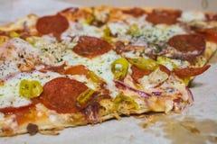 Ορεκτική φέτα της πίτσας με το σαλάμι και την καυτή μακροεντολή πιπεριών Στοκ εικόνα με δικαίωμα ελεύθερης χρήσης