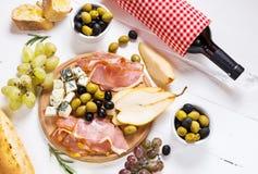 Ορεκτικό, ιταλικό antipasto, ζαμπόν, ελιές, τυρί, ψωμί, σταφύλια, αχλάδι και κρασί στο άσπρο ξύλινο υπόβαθρο Στοκ φωτογραφία με δικαίωμα ελεύθερης χρήσης