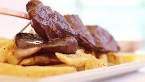 Ορεκτικό καυτό περουβιανό πιάτο βόειου κρέατος καρδιών αποκαλούμενο anticucho με τα τηγανητά απόθεμα βίντεο