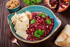 Ορεκτικό με το κόκκινο φασόλι, ξύλο καρυδιάς, βούτυρο, κορίανδρο, μαϊντανός, τσιπ στο πιάτο στο ξύλινο υπόβαθρο τρόφιμα υγιή στοκ εικόνα με δικαίωμα ελεύθερης χρήσης